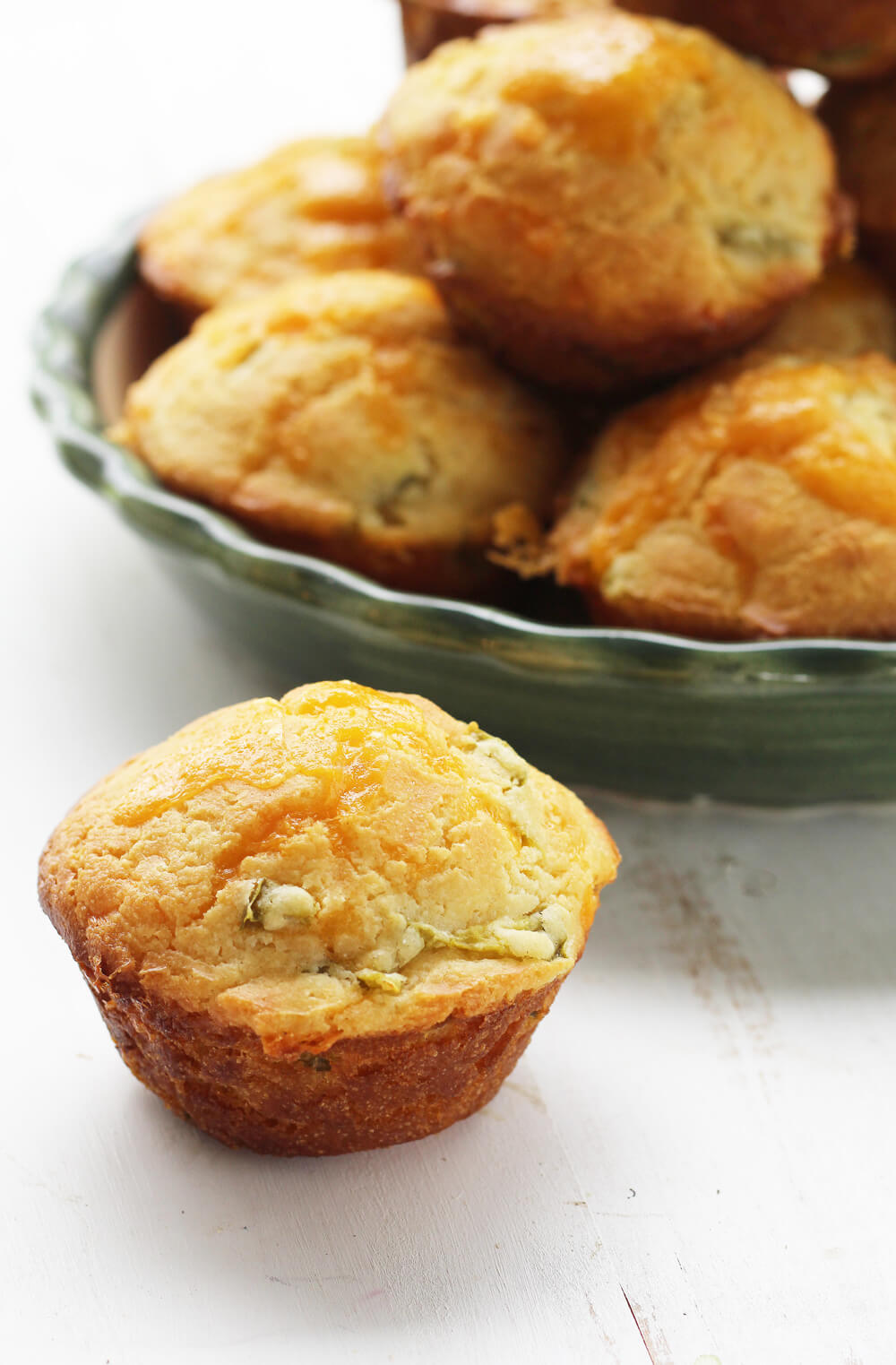 A close up picture of a cornbread muffin with a platter of more muffins in the background