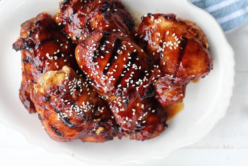 a white platter with sauced grilled chicken sprinkled with sesame seeds