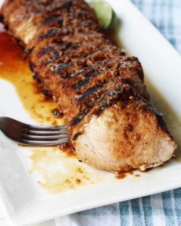 sliced pork tenderloin on a white platter