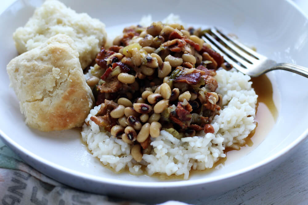 A white dish with rice topped with stewed black eye peas (aka Hoppin John) served with biscuits.
