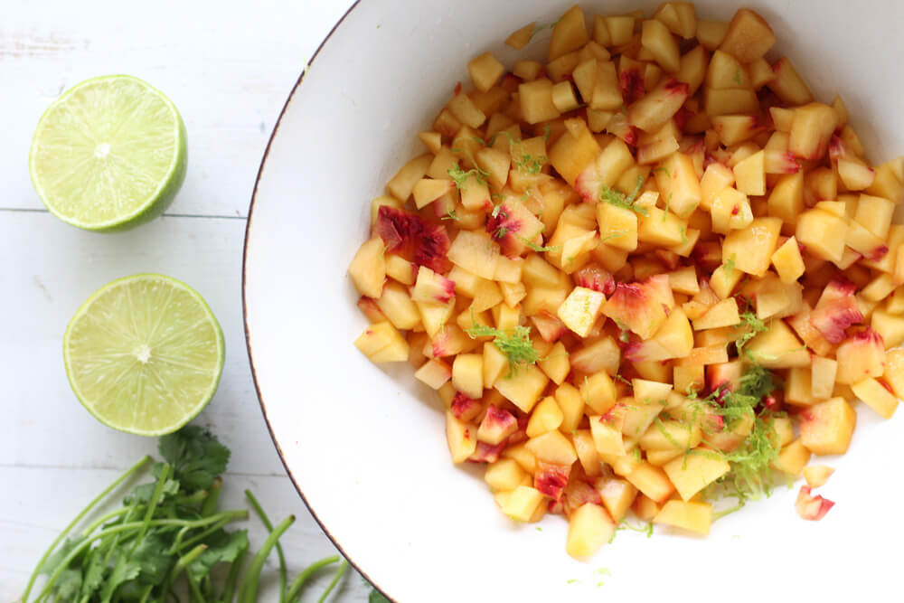 a bowl of fresh, chopped peaches with lime zest and juice