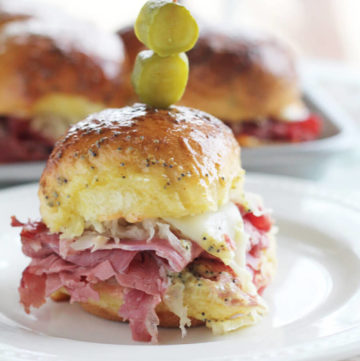 close up picture of a small slider with corned beef, sauerkraut and cheese