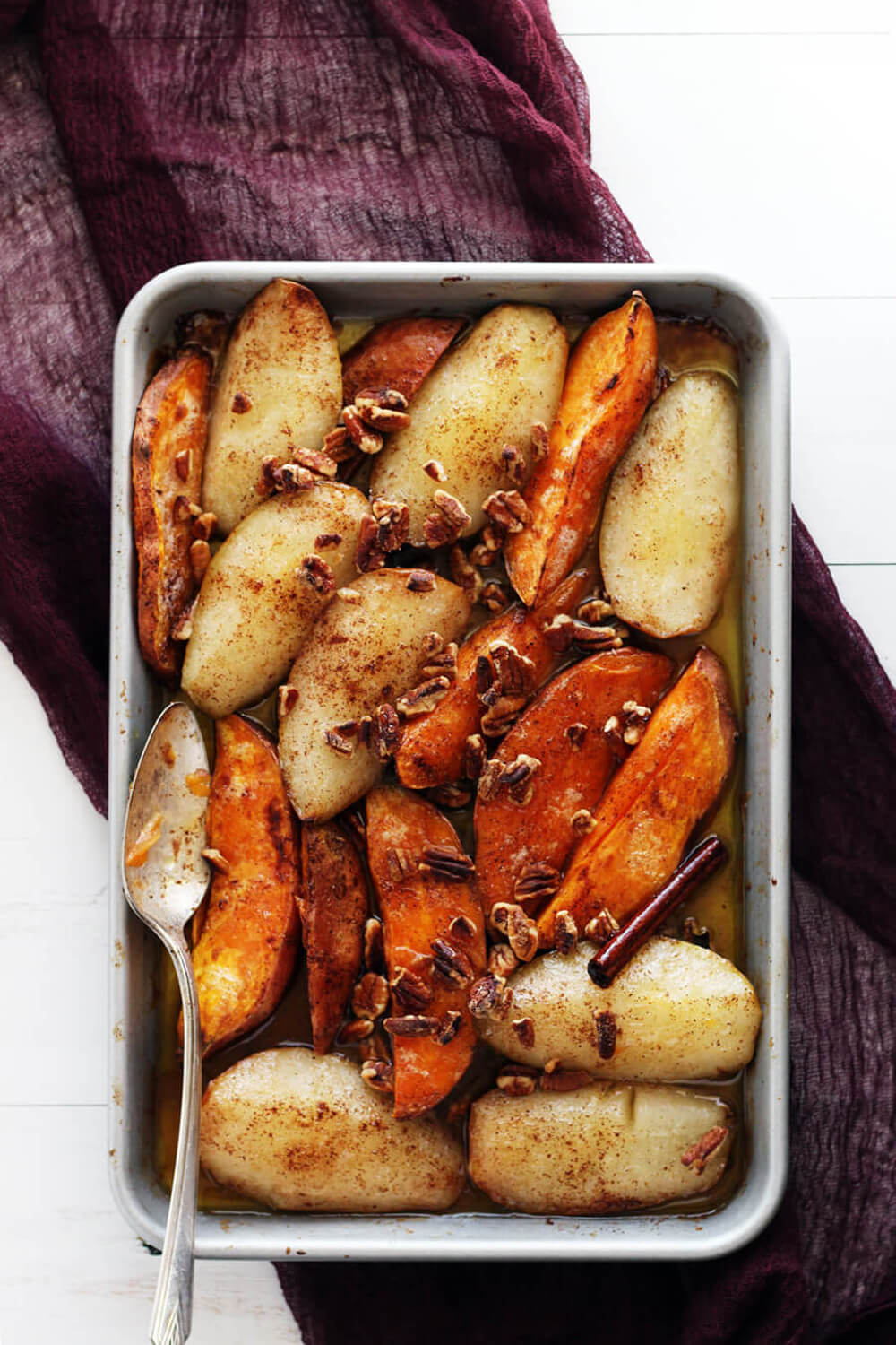 overhead picture of a sheet pan with pears and sweet potatoes with cinnamon and pecans