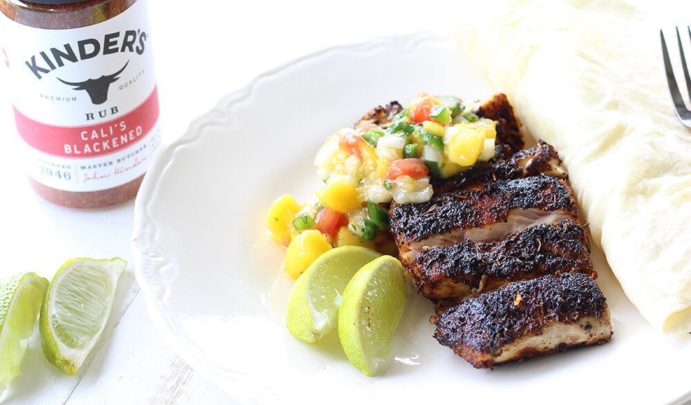 red snapper on a plate with fresh pico and lime