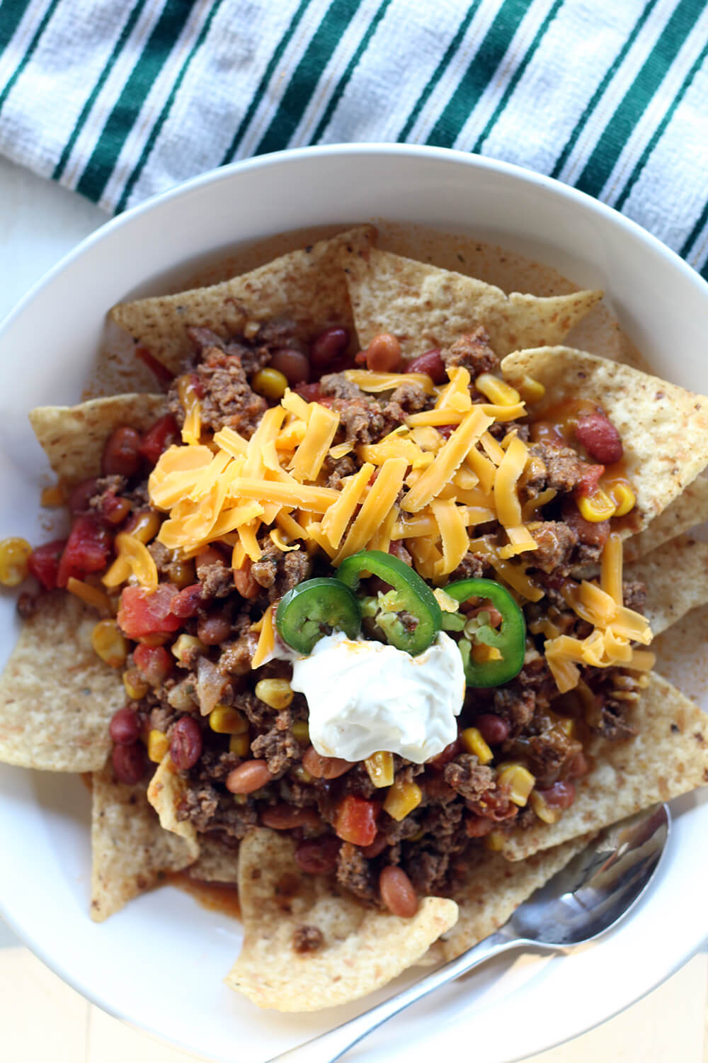 overhead picture of Tex Mex style ground beef mixture on tortilla chips in a white bowl