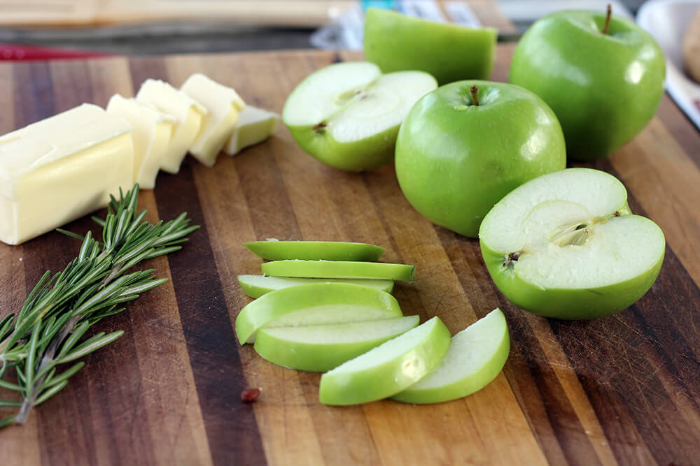 granny smith apples sliced on a wooden cutting board