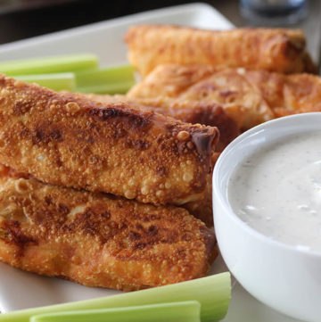 Buffalo Chicken Egg Rolls on a white serving platter served with ranch dressing and fresh celery.