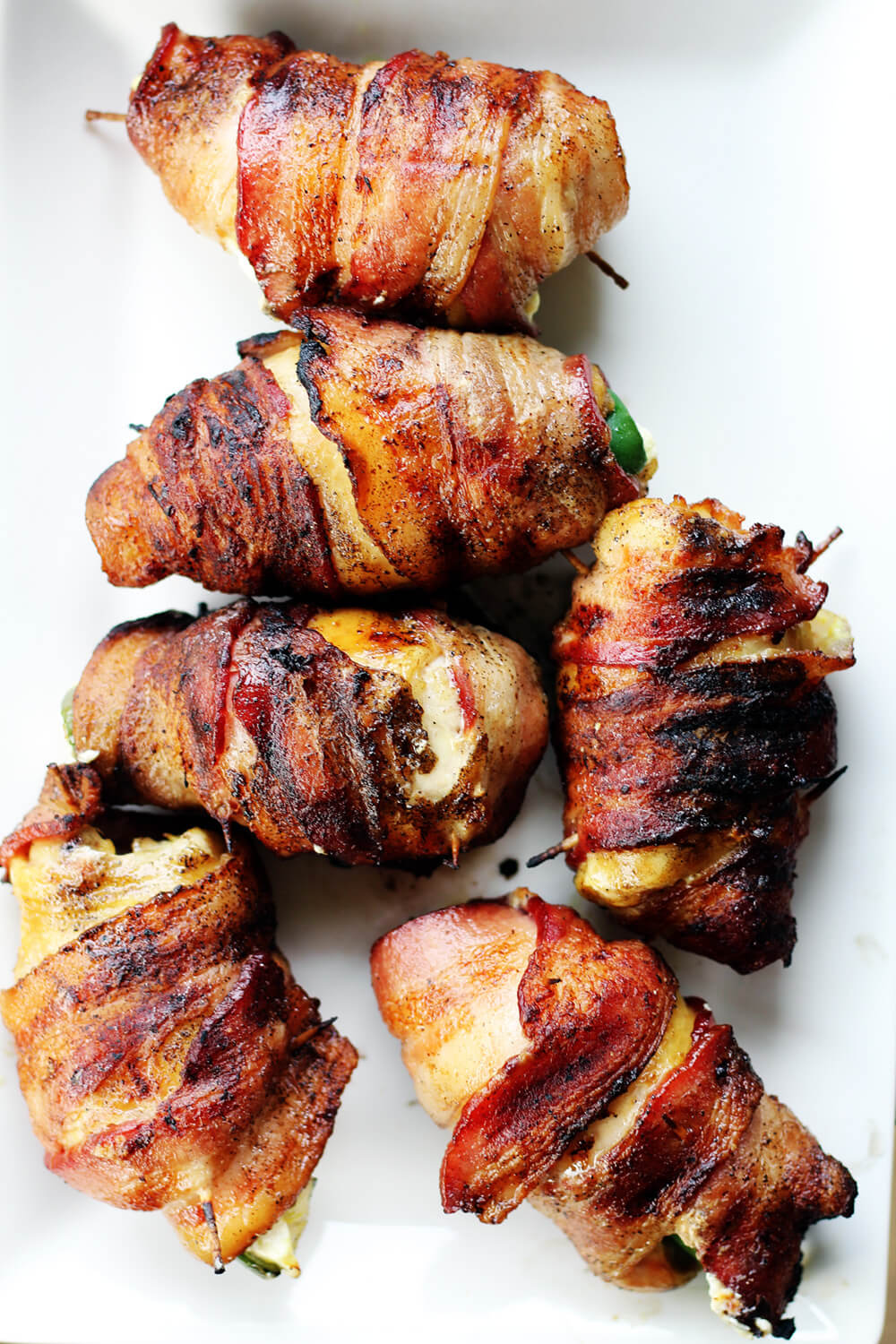 grilled bacon wrapped stuffed chicken on a white serving platter