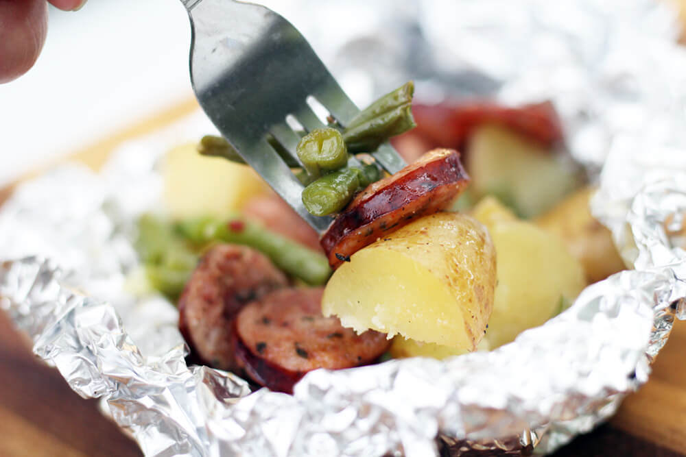 a fork with green beans, smoked sausage, and potatoes