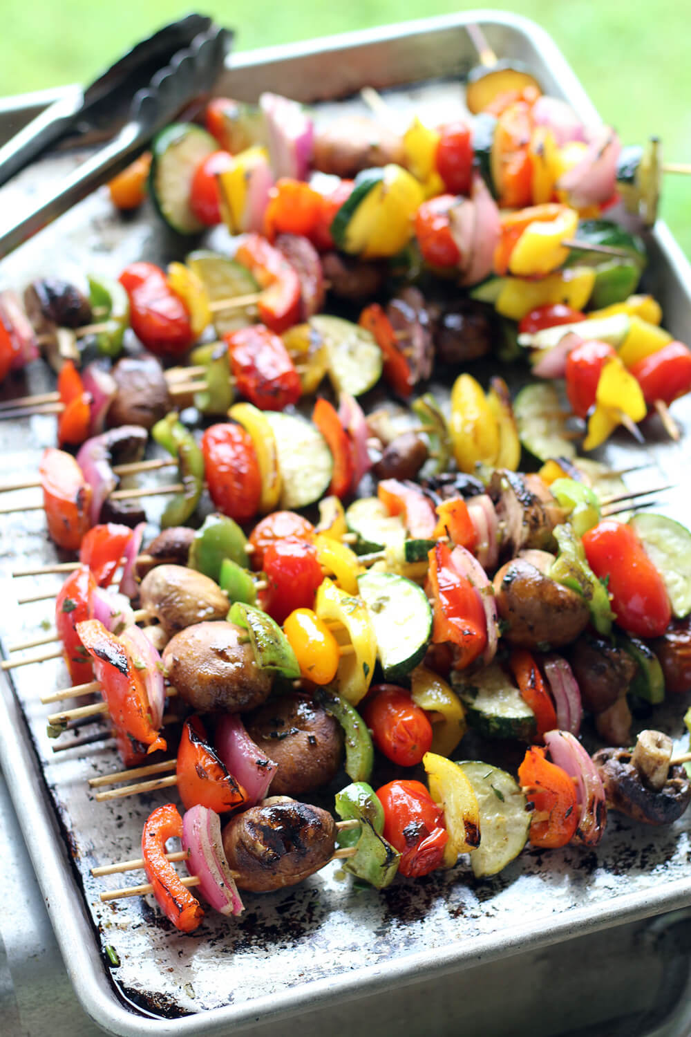 a baking sheet with grilled vegetable kabobs