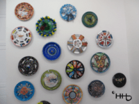 wall of painted original hubcaps for older cars