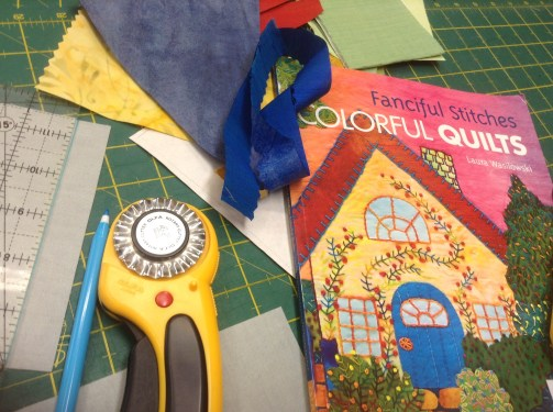 Pinking rotary blade cutter, Laura Wasilowski Fanciful Stitches Colorful quilts book and pieces of fabric with fusible web/appliqué paper ironed on