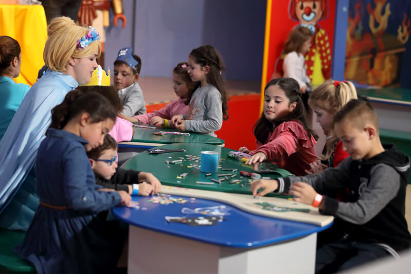 Children building dolls at a Playmobil party.