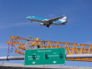 A KLM jet passes over as the Launching Truss walks across the South Arm Bridge.