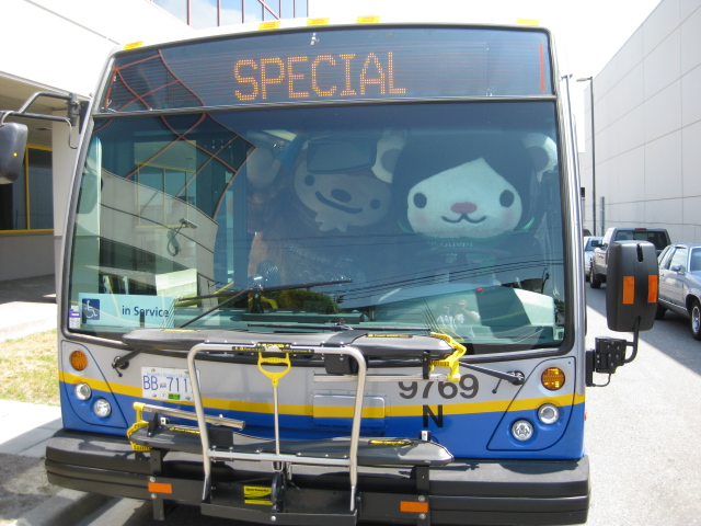 Miga and Quatchi behind the wheel of a bus.