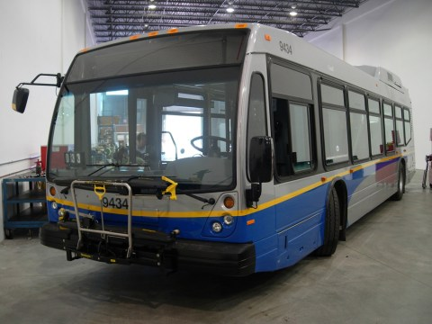 A Nova hybrid bus at the garage, being inspected and tuned up after arriving from the manufacturer.