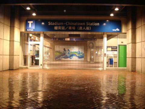 The station entrance name sign at Stadium-Chinatown Station. There's also a T beacon on a pole outside.