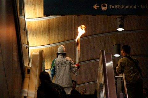 The Olympic torchbearer heads up the escalator onto the train. Photo by <a href=http://www.flickr.com/photos/theducks/4344758411/in/set-72157623395553502/>Alex Dawson</a>