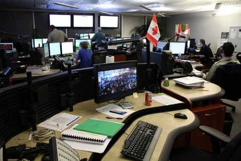 A monitor on one desk displays a live-cam from downtown Vancouver, so T-Comm can monitor the movements of crowds.