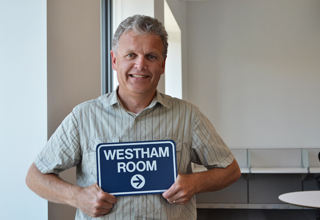 Bob holding a sign to a TransLink meeting room with the same name as the bridge.