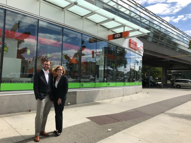 Guy Akester, TransLink's Director of Real Estate Programs and Partnerships with Patti Parente, Vice-President of Real Estate for A&W Food Services Canada outside the new 24-hour A&W restaurant at Main Street–Science World Station.