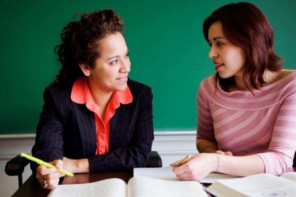Teacher teaching student in classroom
