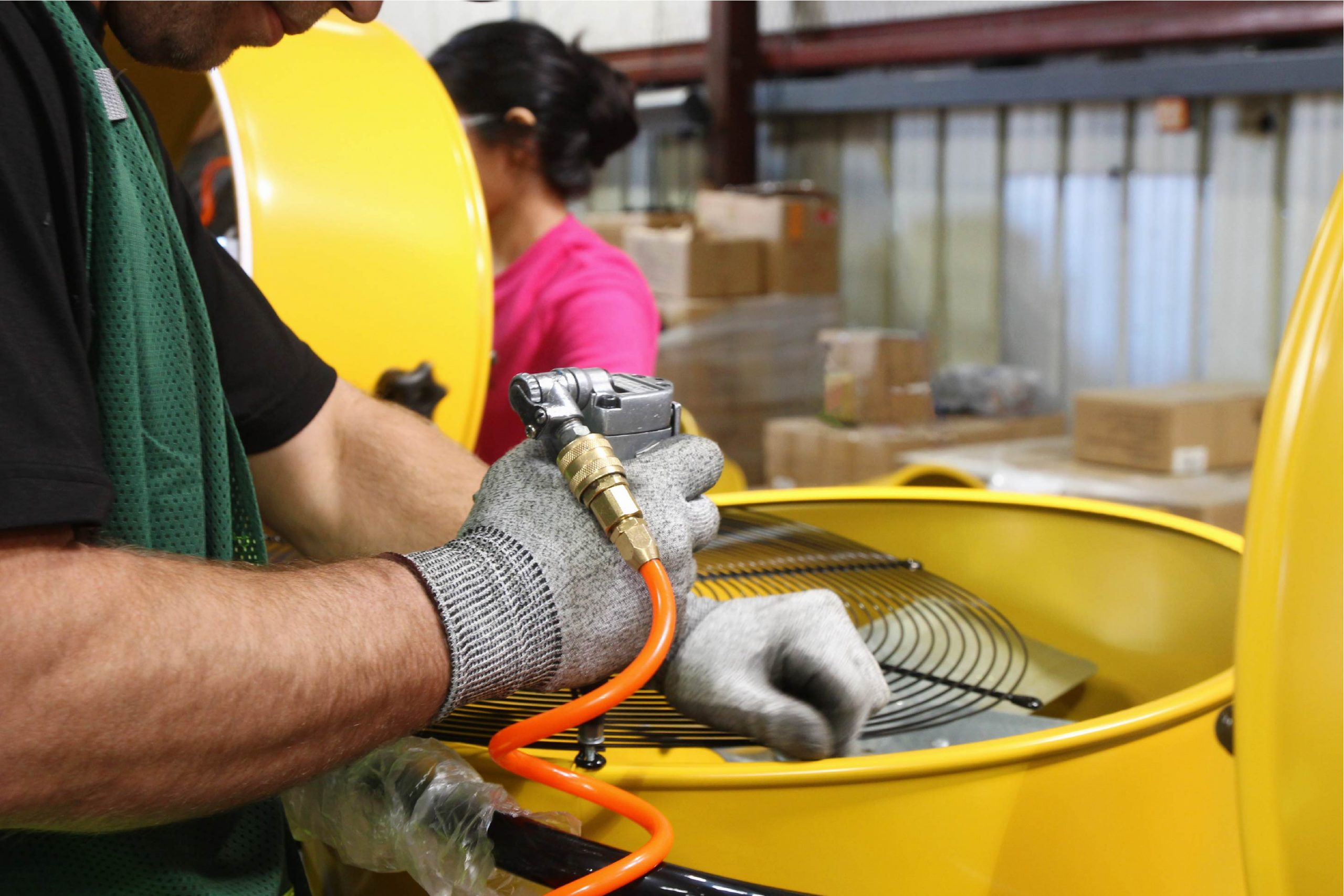 Employee fastens a grille to the yellow steel housing of a Maxx Air drum fan.