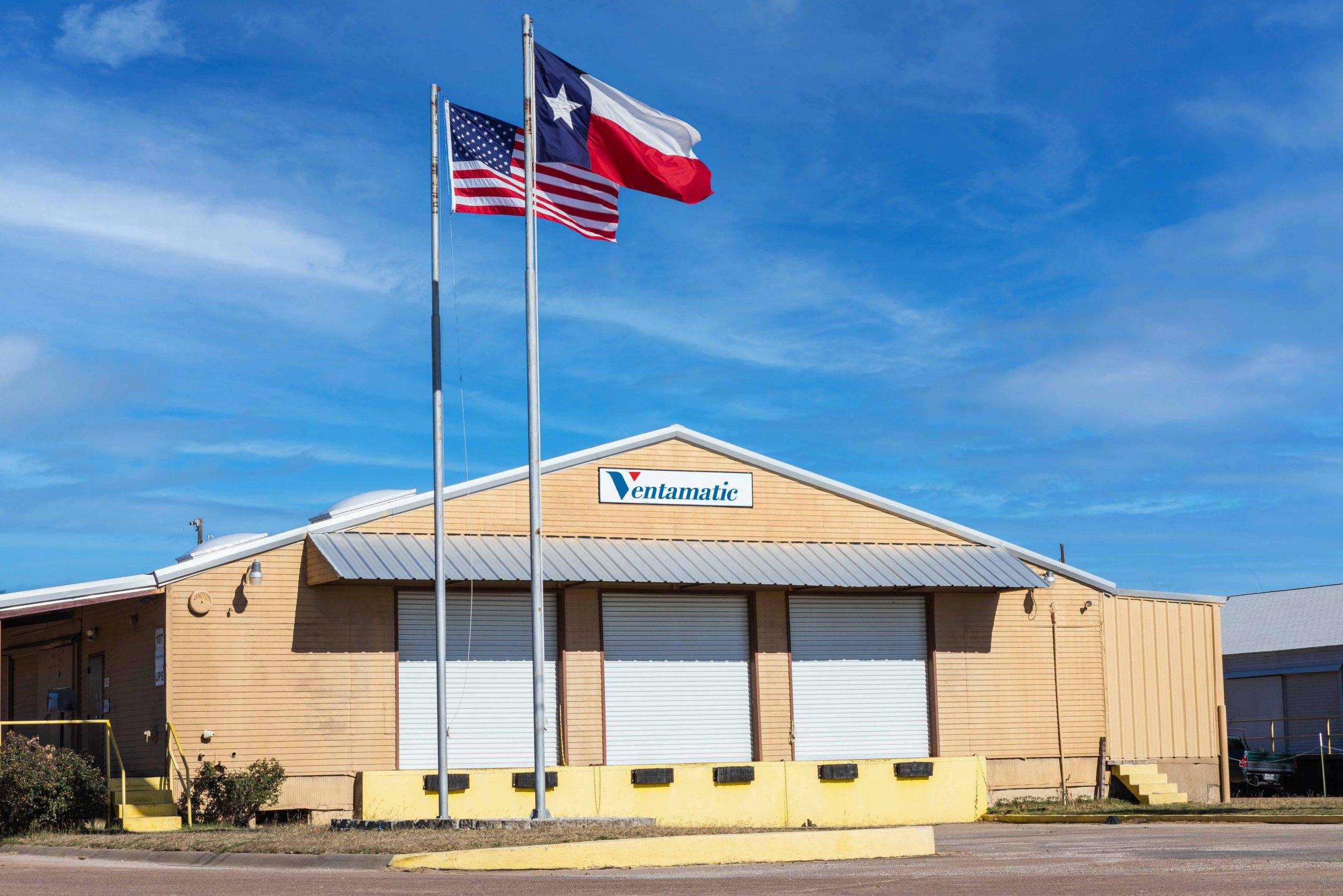 Ventamatic's shipping warehouse with US and Texas flags flying outside.