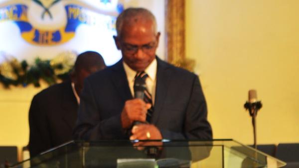 A praying Reverend Dr Job Webb from Calvery Wesleyan Holiness Church