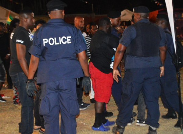 Police restraining a college student (not visible in the photo) during the Virgin Gorda Easter Festival Monday morning