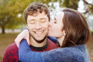 Kobieta całuje mężczyznę w policzku