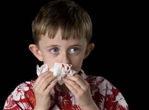 мальчик держит платок с кровью у носа