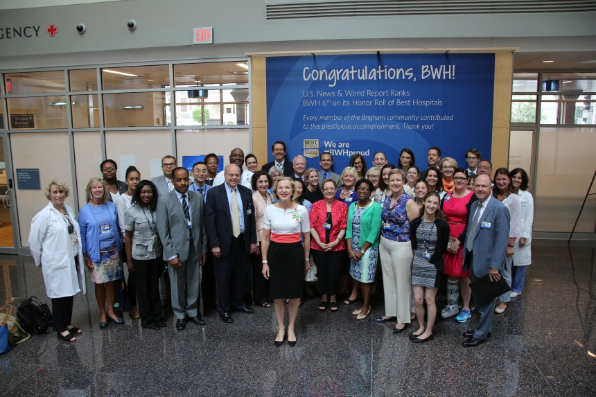 BWHers including President Betsy Nabel gather in front of the hospital's celebratory wall, where all are welcome to take a photo for six weeks.
