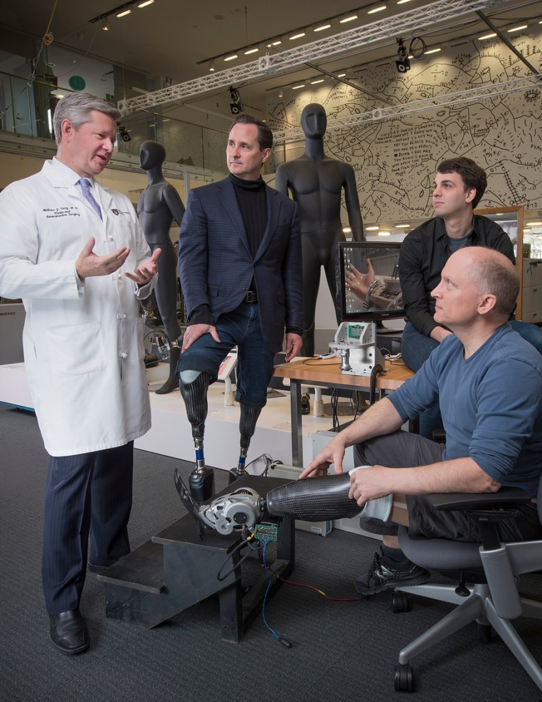 Matthew J. Carty, MD, of BWH (left), confers with Hugh Herr, PhD (center), and Tyler Clites of MIT, as Jim Ewing (foreground) tests their newly developed prosthetic device. (Photo by Stu Rosner)