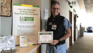 Stewart Fenniman poses with a DAISY award poster