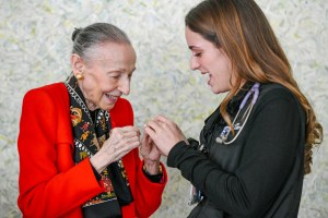 Estrellita Karsh gives Rachel Colby, BSN, RN, of Shapiro 9/10, her angel wings pin during a special luncheon for NLNs. Colby, who addressed fellow NLNs, preceptors and leaders, said the Nora McDonough Newly Licensed Nursing Program helped ease her fears and showed her how supported NLNs are at the Brigham.