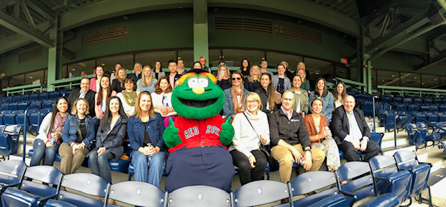 Conference attendees gather with Boston Red Sox mascot Wally in Fenway Park.