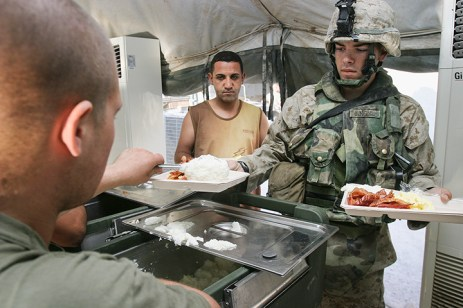 Marine and Iraqi interpreter in serving line for breakfast — including bacon and grits — at Forward Operating Base Iskandariyah, Babil Province, August 10, 2004