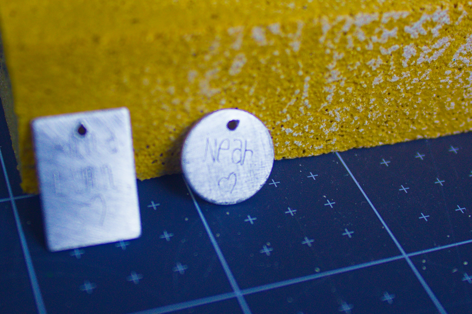 cricut engraving tool engraved charms sitting against a yellow sanding block