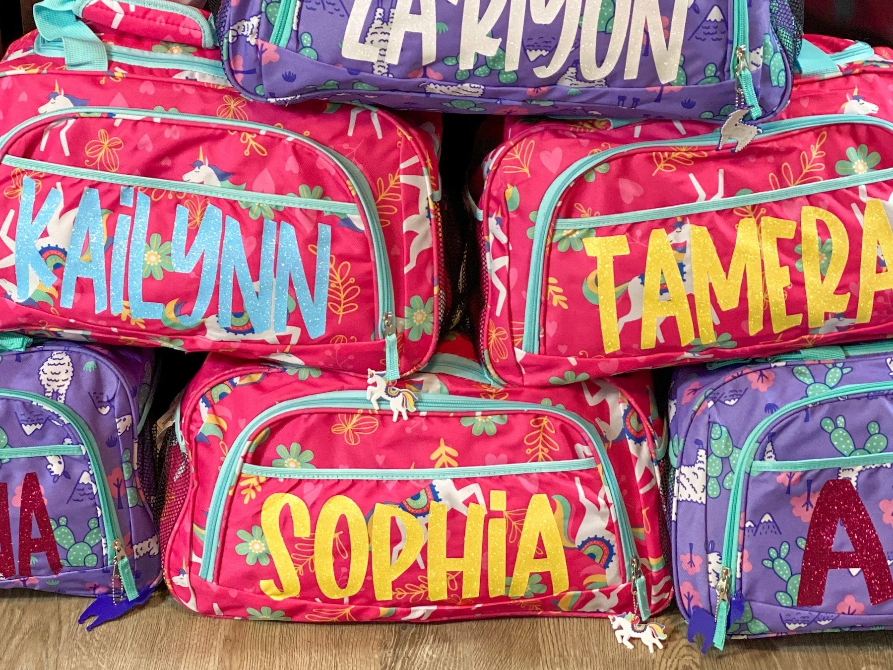 pink and purple kids duffel bags with names made with the cricut easypress mini