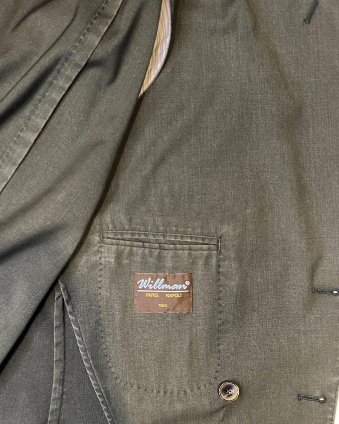 """""""Costume en laine lavée kaki, 6 boutons, avec 4 boutonnières ouvertes, deux fentes, poches plaquées, sans doublure. Surpiqures pour un côté plus sport avec un effet délavé dû au lavage. Pantalon avec pattes de serrage, braguette avec zip et patte de boutonnage cachée sur le côté, longueur à retoucher. Coupe ajustée, bas à 17cm sur une taille 46. Le mot de Norbert : Un costume pouvant se porter d'une manière dépareillée, ultra léger, idéal pour toutes les ambiances estivales"""""""