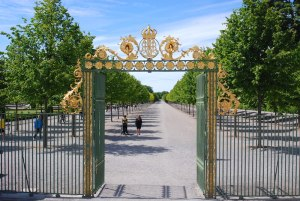 The green and golden baroque style iron gate entrance to Drottiningholm Palace Park's wide esplanade. By C.S. White