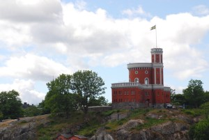 The small, red and white Kastellet on Kastellholmen, Stockholm, stands alone on a rocky point. By C.S. White