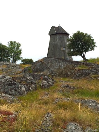 A small wooden millhouse atop a mostly stark, craggy hill on Toro, Stockholm, Sweden. By C.S. White
