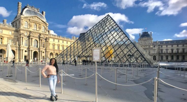 standing in front of the Louvre after traveling to Paris