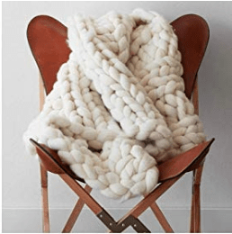 A COZY KNIT BLANKET PROPPED UP ON A CHAIR