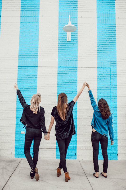 three girls holding hands in front of painted wall for their bachelorette party planning.