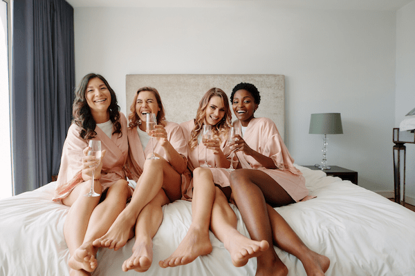 girls lounging on the bed in matching robes. take this bachelorette party advice- matching bachelorette swag makes for a good time!