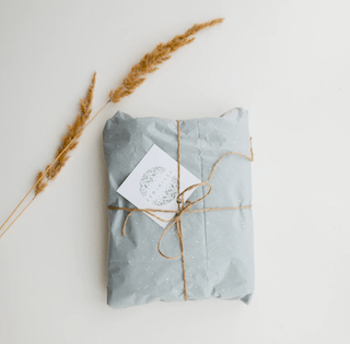 light blue subscription box package with a card attached