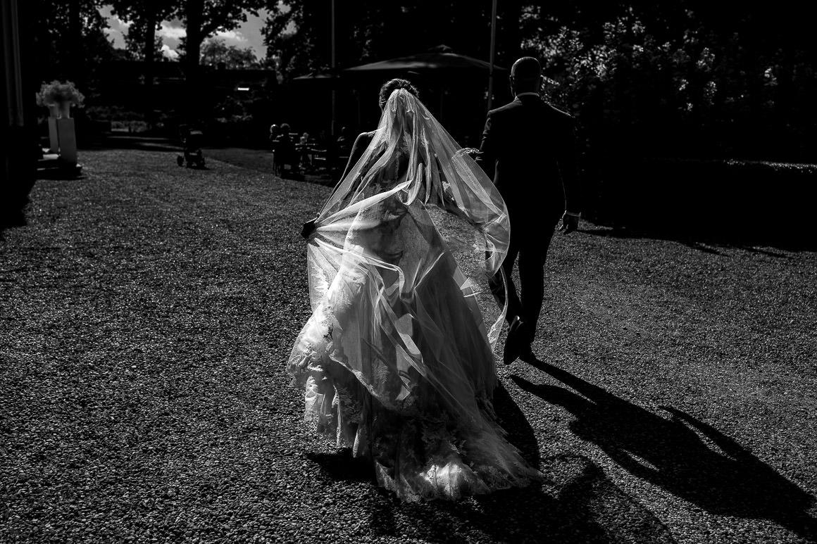 een foto van het bruidspaar met prachtig licht waardoor de jurk licht lijkt te geven